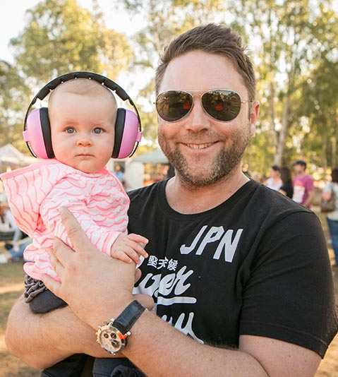 Father holding young child with headphones on at a music event, Packer Park, Carnegie