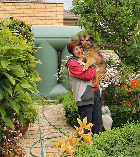 Woman holding her dog in her garden